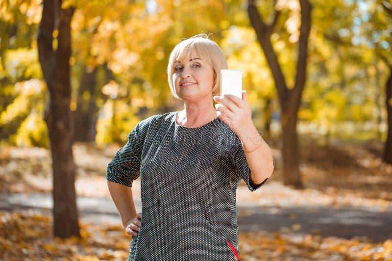 做在秋天公园背景的妇女selfie  正面图 免版税库存图片