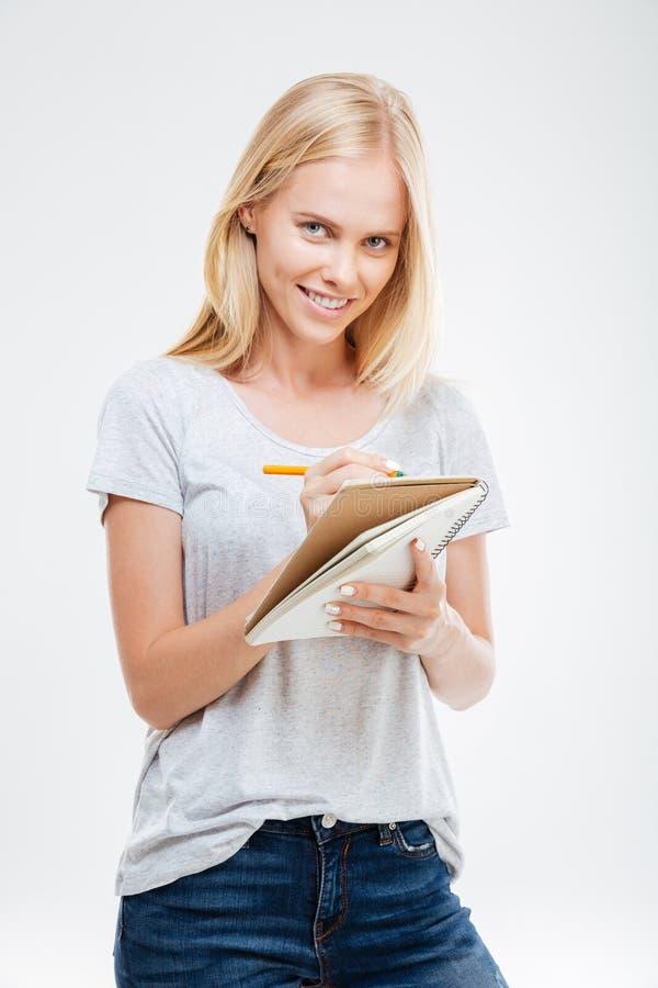 做在笔记薄的一个微笑的女孩的画象笔记 库存照片