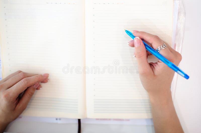 做在笔记薄的女商人笔记 美好的穿着考究的手特写镜头手,拿着笔 图库摄影