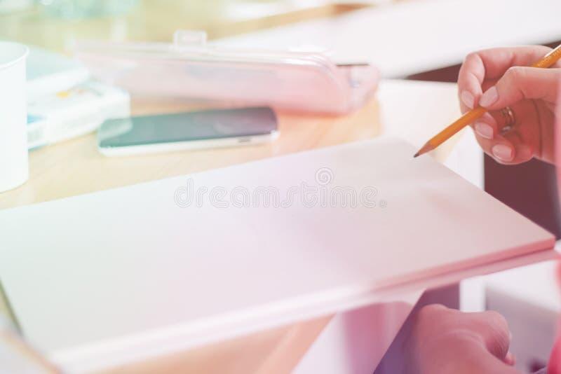 做在笔记薄的女性手特写镜头笔记在办公室,轻定调子 免版税库存图片