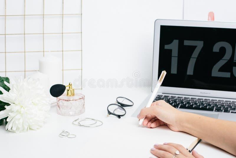 做在笔记薄的女性手笔记在与膝上型计算机键盘的一张白色桌 库存照片
