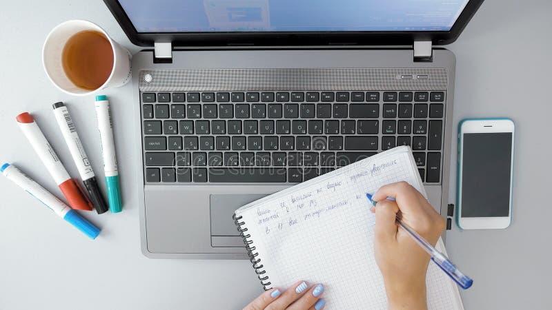 做在纸笔记本的女性手笔记由笔 免版税库存图片