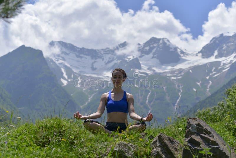 做在绿草的年轻体育妇女瑜伽在夏天 免版税库存照片