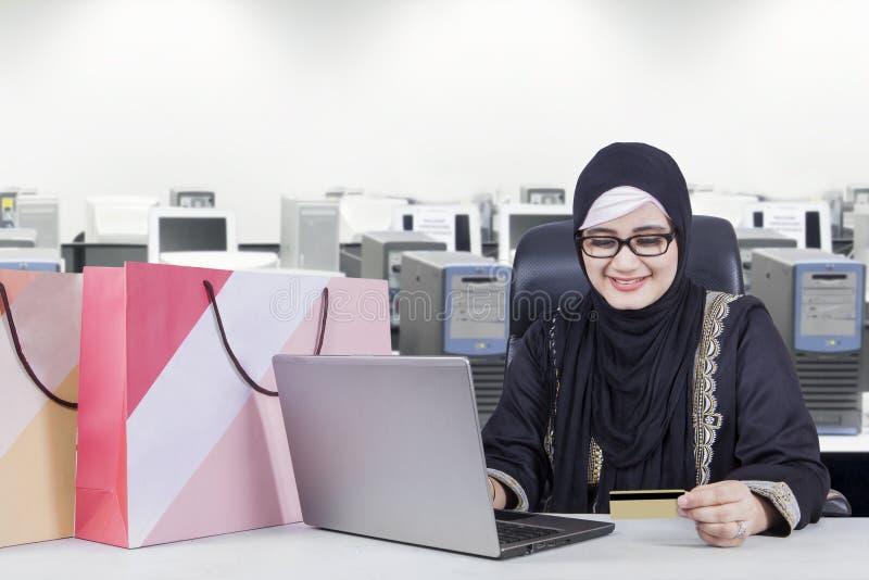 做在网上购物的女实业家在办公室 库存图片