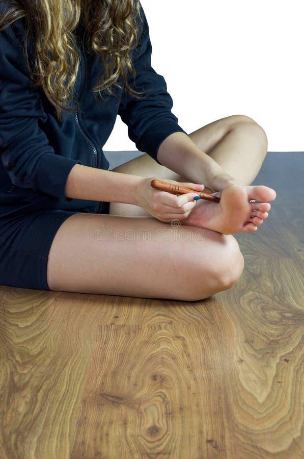 做在脚的脚底的妇女压力用一根木棍子 免版税库存图片