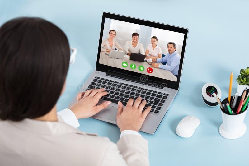 做在膝上型计算机的女实业家电视电话会议 库存照片