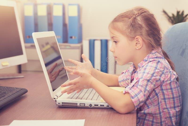 做在膝上型计算机的小女孩家庭作业 免版税库存图片