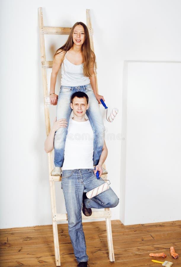 做在自己的舱内甲板的愉快的年轻新的家庭画象修理,在梯子,生活方式人概念附近结合 免版税图库摄影
