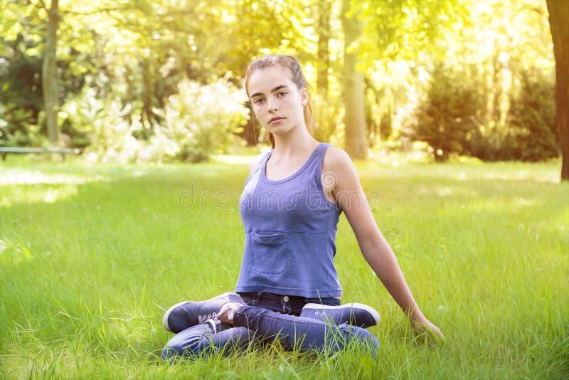 做在自然的少妇瑜伽 库存图片