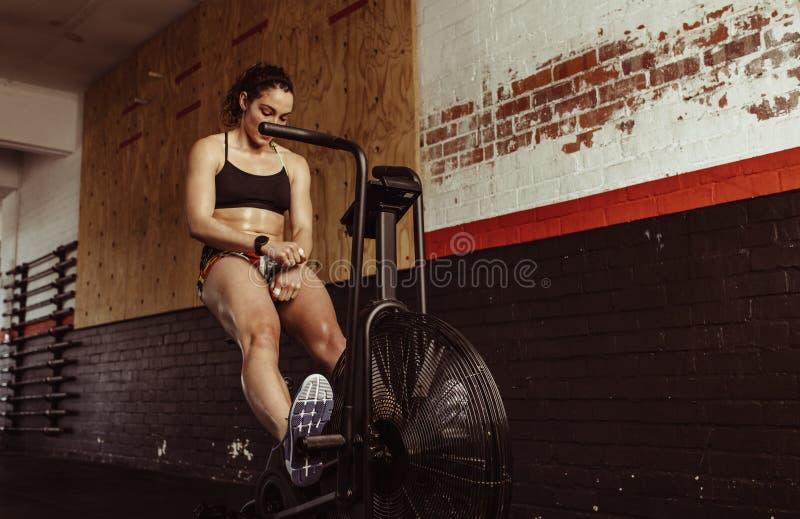 做在自行车的妇女心脏锻炼在健身房 免版税库存照片