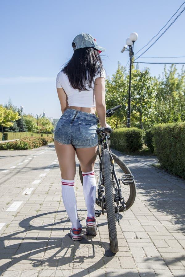 做在自行车的少妇体育 免版税库存图片