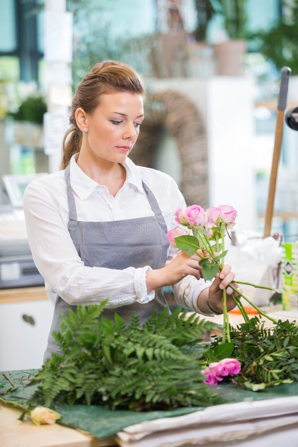 做在花店的卖花人罗斯花束 免版税库存照片