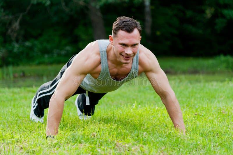 做在草的人健身锻炼 免版税图库摄影