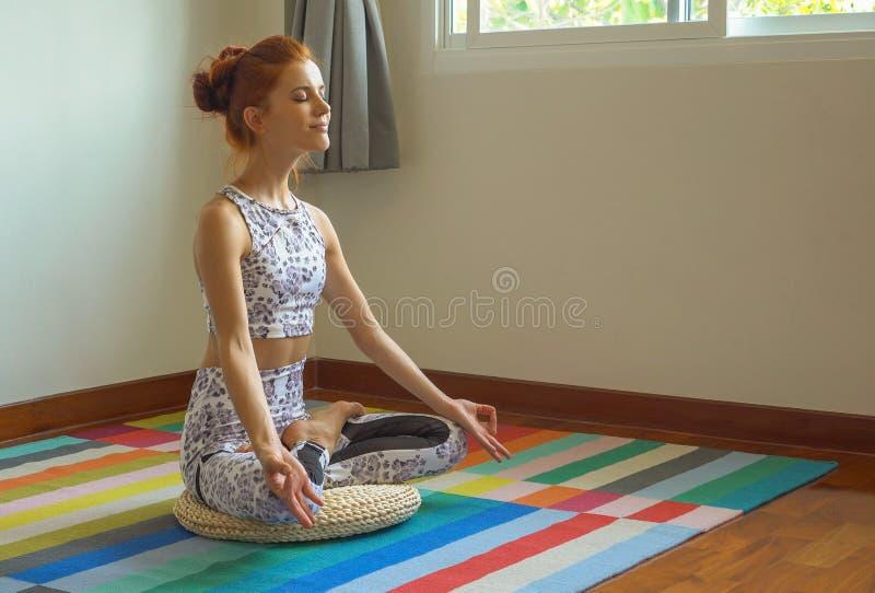 做在莲花坐的运动的年轻女人瑜伽实践在席子在家,健身女孩锻炼在屋子里 免版税库存图片