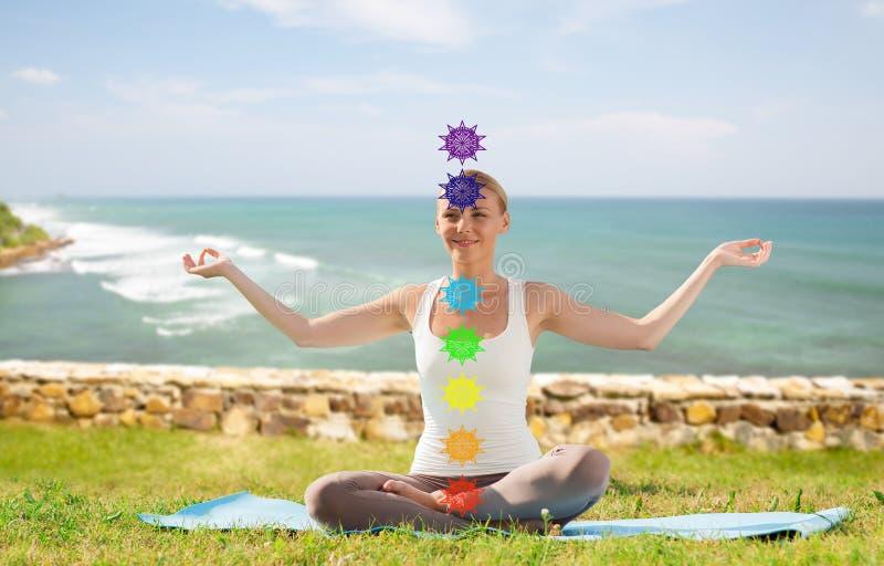 做在莲花姿势的妇女瑜伽与七chakras 库存照片