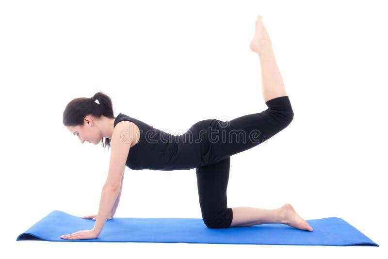 做在蓝色瑜伽席子的年轻可爱的妇女健身锻炼我 库存图片