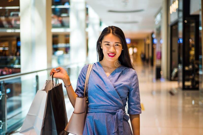 做在购物中心的愉快的女孩购物 库存图片