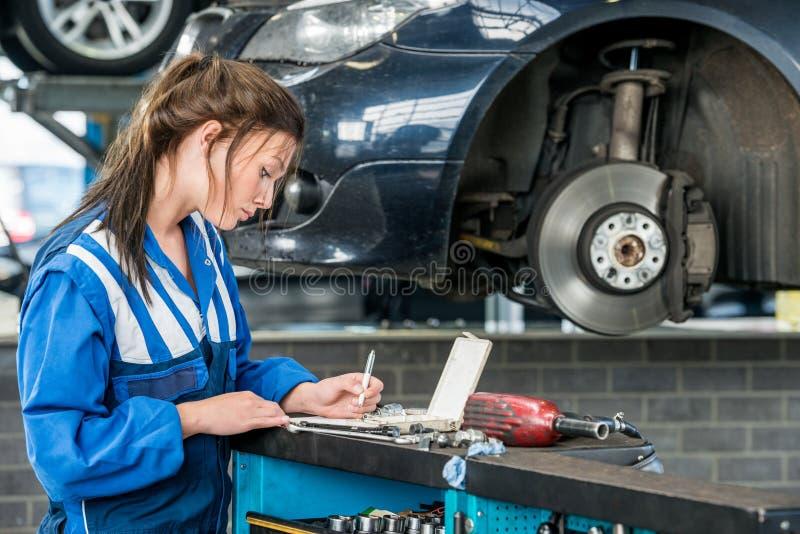 做在车库的年轻女性技工笔记 免版税库存图片