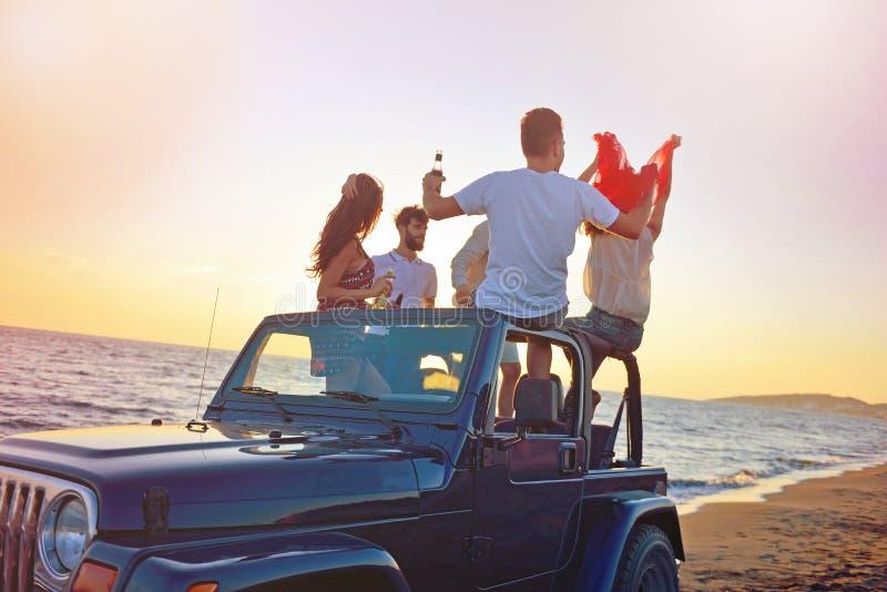 做在车的青年人的小组愉快的朋友党食用乐趣饮用的香槟 免版税库存照片