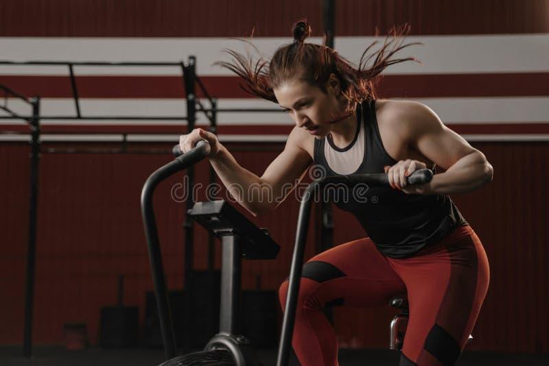 做在锻炼脚踏车的体育妇女强烈的心脏训练在crossfit健身房 库存图片