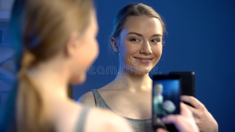 做在镜象反射的社会网,乐趣的美丽的少女selfie 免版税库存图片