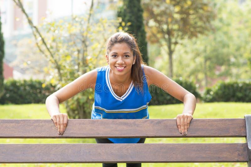 做在长凳的微笑的运动妇女俯卧撑 免版税库存图片
