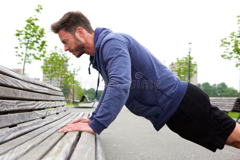 做在长凳的英俊的人pushup 免版税库存照片