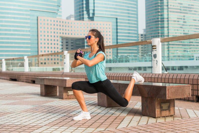 做在长凳的运动的女运动员唯一腿刺锻炼 解决户外在城市胡同的适合的少妇 库存图片