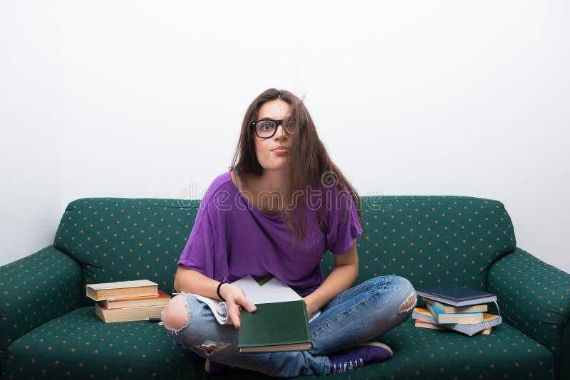 做在长沙发的聪明的大学生家庭作业 图库摄影