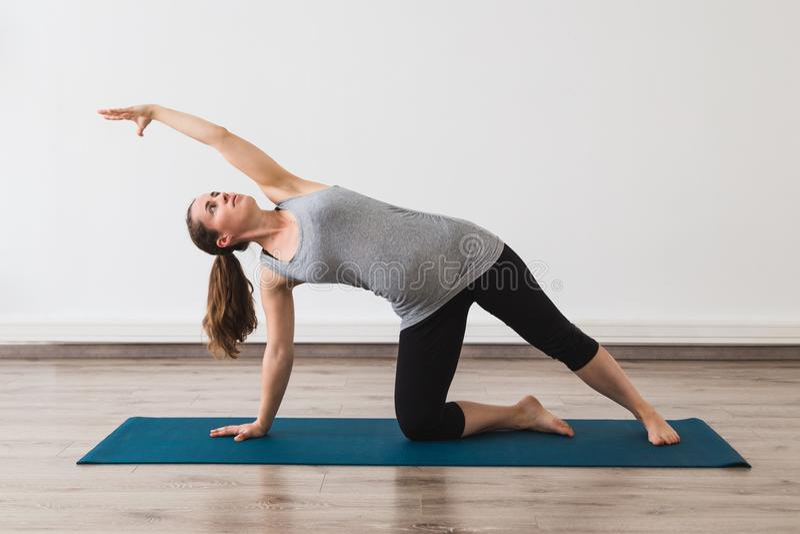 做在门姿势的少妇怀孕瑜伽 免版税库存图片