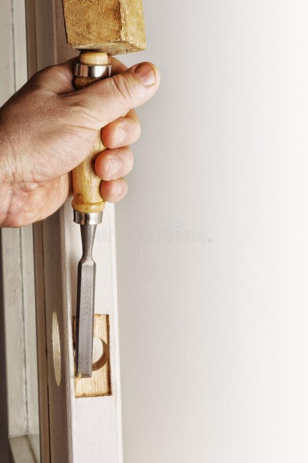 做在门的槽孔,与凿子 免版税图库摄影