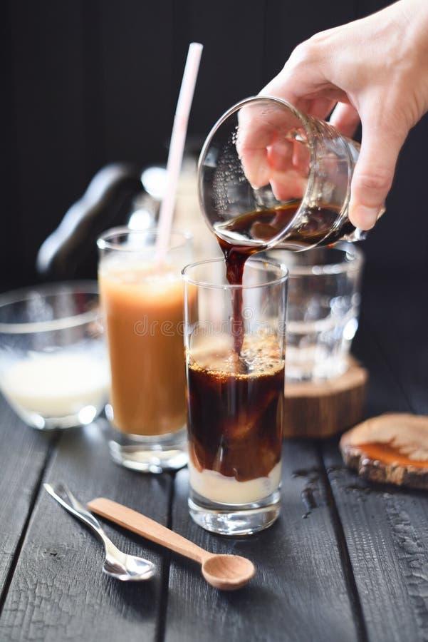 做在高玻璃的冰冻咖啡 倒在冰块和浓缩牛奶的妇女手无奶咖啡在黑背景 图库摄影