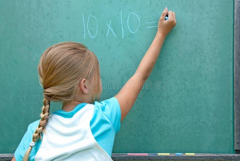 做在黑板的白种人女孩算术 库存照片