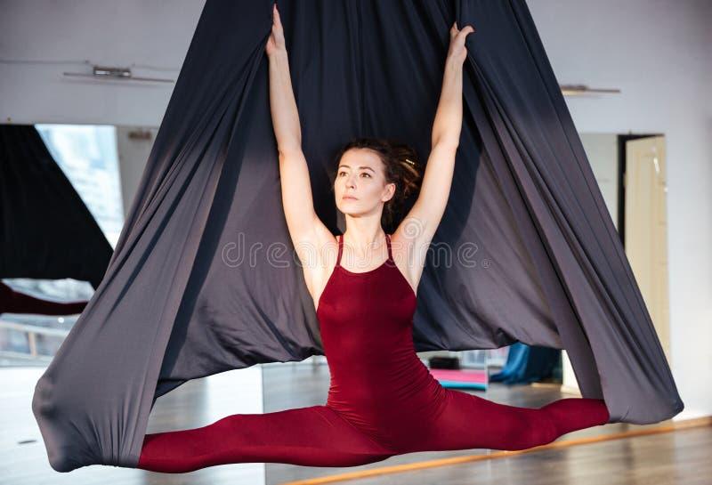 做在黑吊床的Beautiul少妇空中瑜伽 免版税库存图片