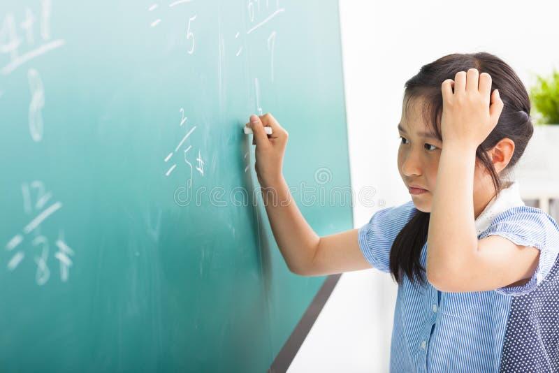 做在黑板的女孩数学题 免版税库存照片