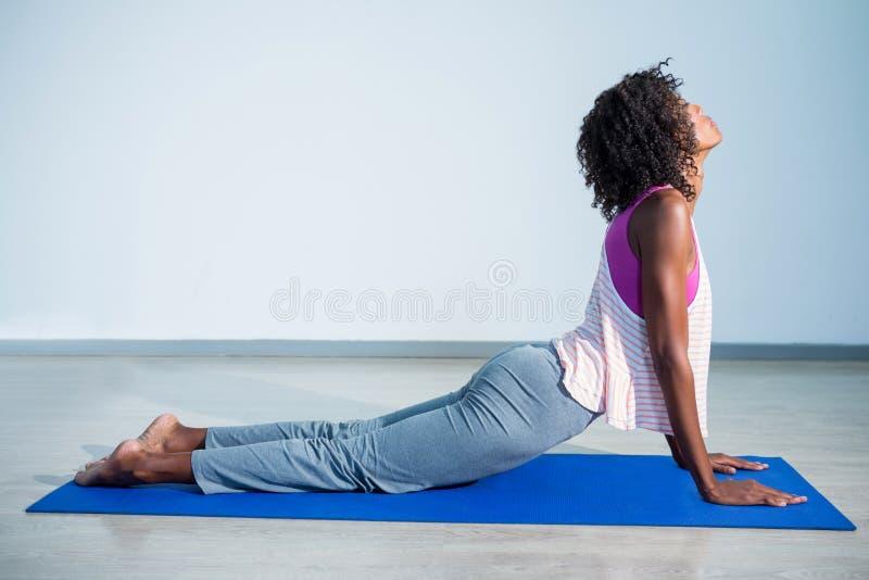 做在锻炼席子的妇女眼镜蛇姿势 免版税库存图片