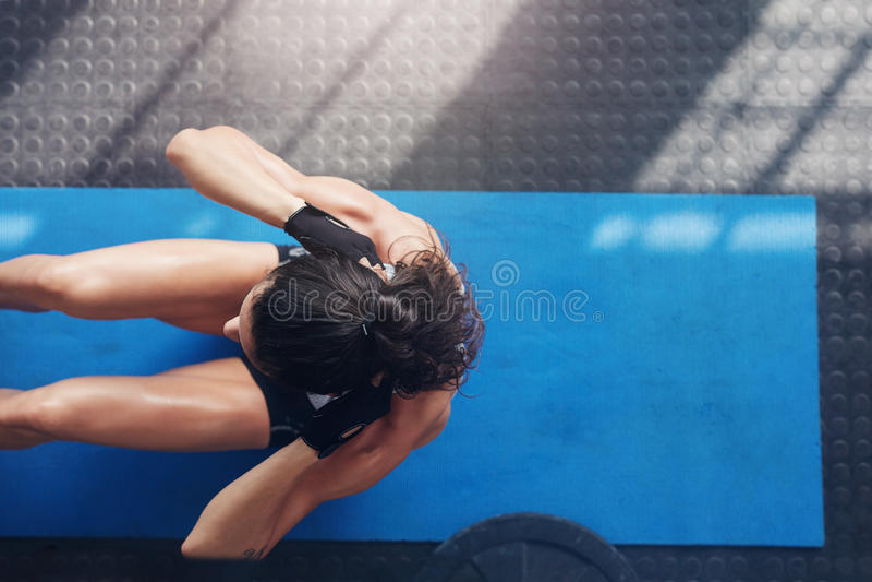 做在锻炼席子的肌肉少妇仰卧起坐 免版税库存图片