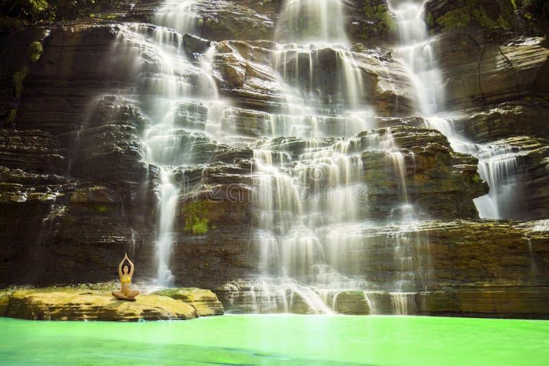 做在Cigangsa瀑布的少妇瑜伽 免版税库存图片