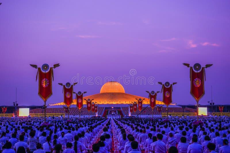 做在Dhammakaya Cetiya前面的许多佛教徒凝思 免版税库存图片