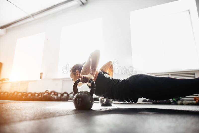 做在kettlebells的妇女俯卧撑锻炼 十字架适合的训练 库存图片