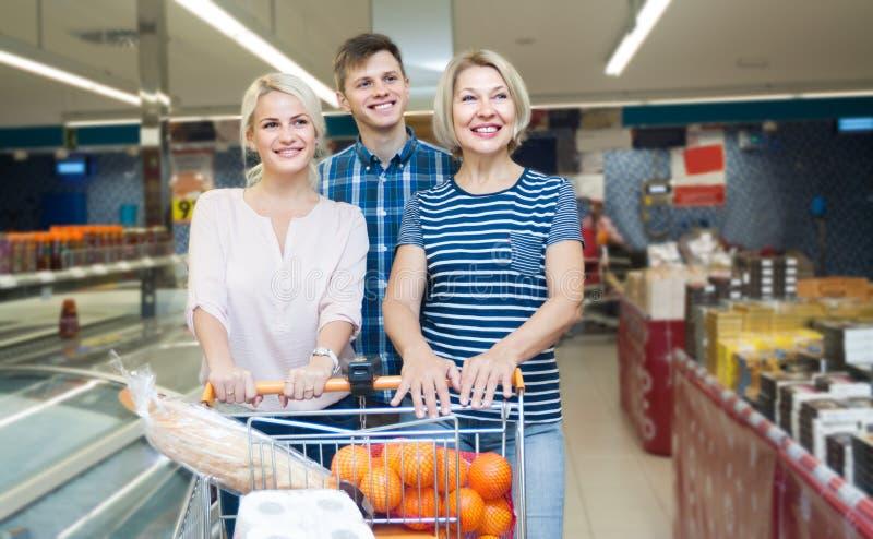 年轻做在supermarke的家庭和一名年长妇女购物 免版税图库摄影