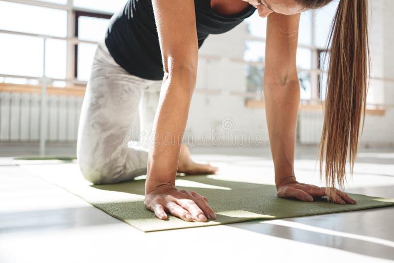 做坚强的运动的妇女舒展在瑜伽席子的锻炼在晴朗的白色健身房 图库摄影