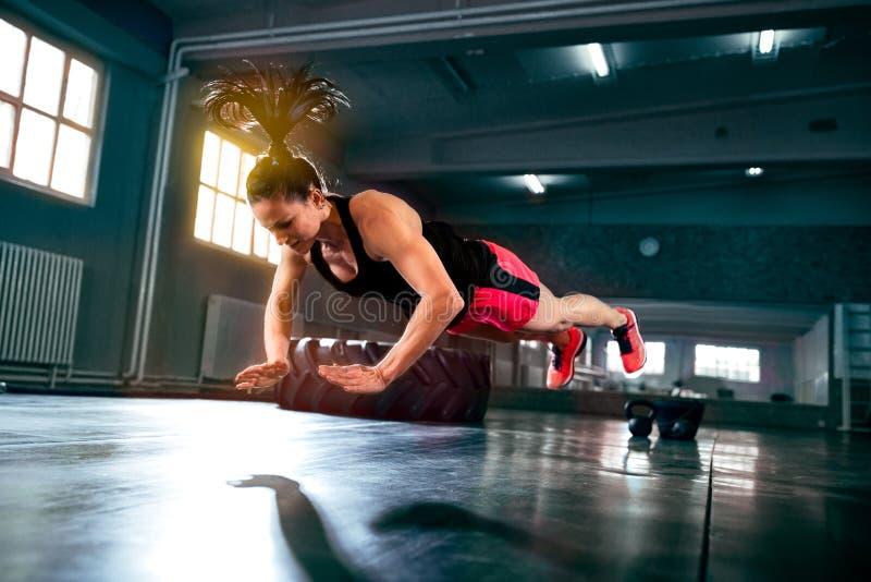 做坚硬强烈的锻炼的坚强的强有力的妇女在健身房 库存照片