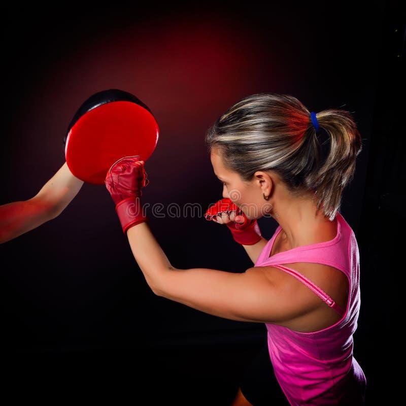 做坚硬拳打的少妇在训练期间 免版税库存照片