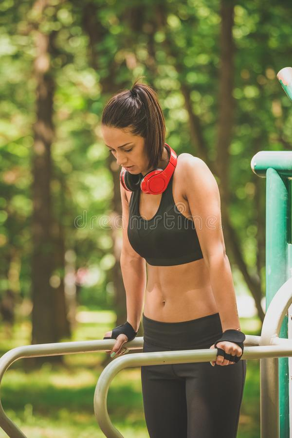 做垂度的美丽的健身妇女在公园行使 免版税库存图片