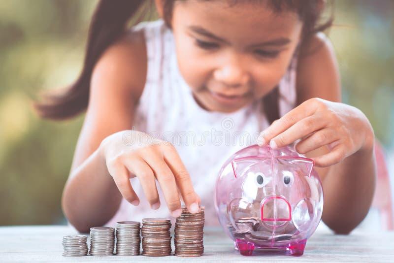 做堆硬币和放金钱的亚裔女孩入存钱罐 免版税库存图片