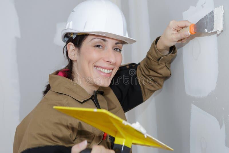 做墙壁整修的女性石膏工画家 库存图片