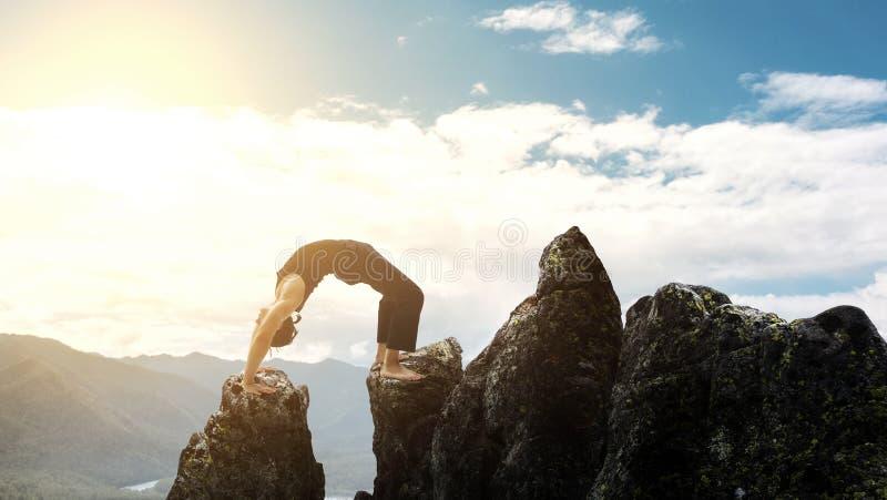 做复杂瑜伽锻炼headstand的人 在美丽的山的惊人的瑜伽风景 危险特技traceur 免版税库存图片