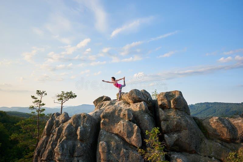 做复杂的瑜伽姿势的年轻亭亭玉立的妇女在夏天巨大的岩石之前太阳上面点燃了 库存照片