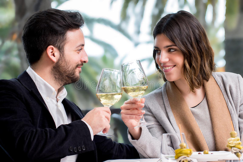做多士用白葡萄酒的典雅的夫妇在餐馆 免版税库存照片